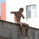 "Artist Pyotr Pavlensky cuts off a part of his earlobe sitting atop wall in protest action titled ""Segregation"" in Moscow"