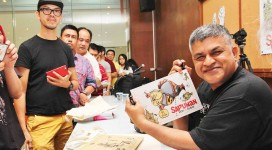 Zunar signs copies of his latest collection of cartoons in Kuala Lumpur on Sunday (Facebook.)