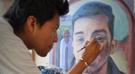 A member of the 43 Artist Group is pictured working on the portrait of one of the 43 students killed on their way to a protest (CNN.)